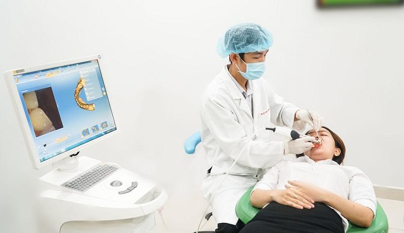 Bác sĩ kiểm tra răng cho khách hàng bằng hệ thống máy Cerec