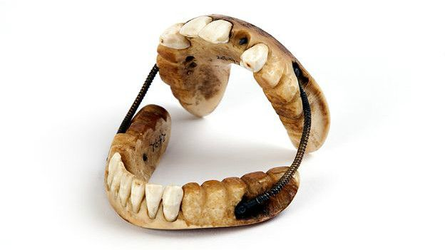 bộ răng giả làm từ ngà voi, gồm hàm trên và hàm dưới được kết nối với nhau bằng các lò xo piano.